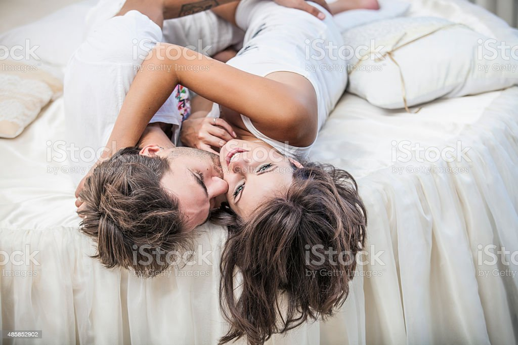 Couple man and woman lay cuddling on the bed stock photo