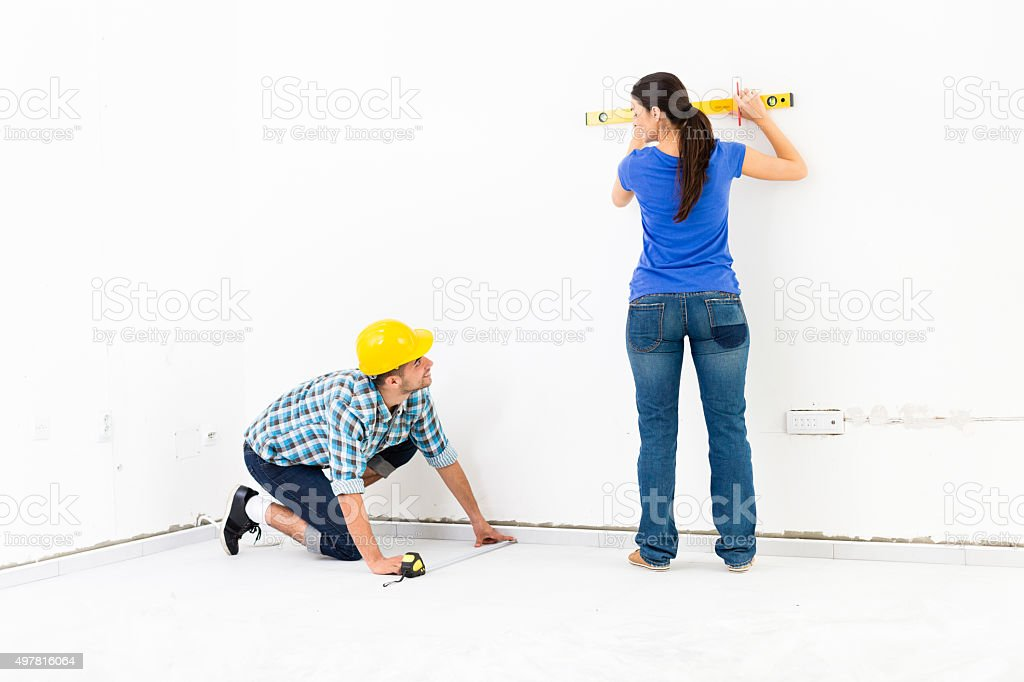 Couple measuring the wall in their new home stock photo