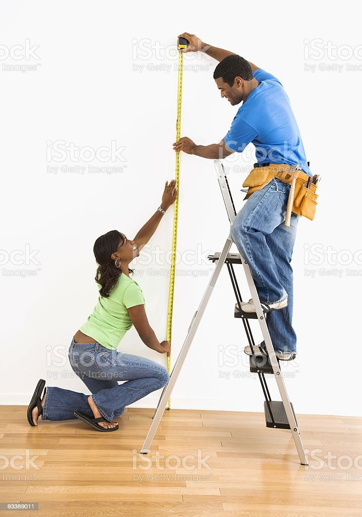 Couple measuring wall. royalty-free stock photo
