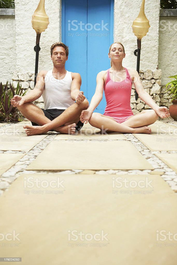 Couple Meditating Outdoors At Health Spa royalty-free stock photo