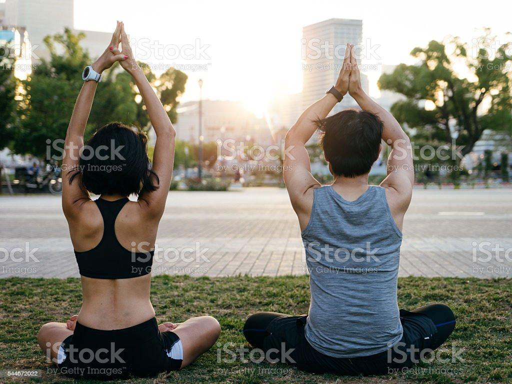 Couple Meditating Under The Bridge At Sunset stock photo