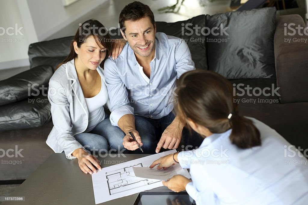 Couple meeting adviser for property purchase stock photo