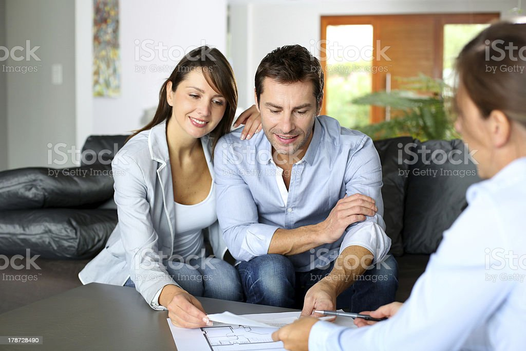 Couple meeting architect at home stock photo