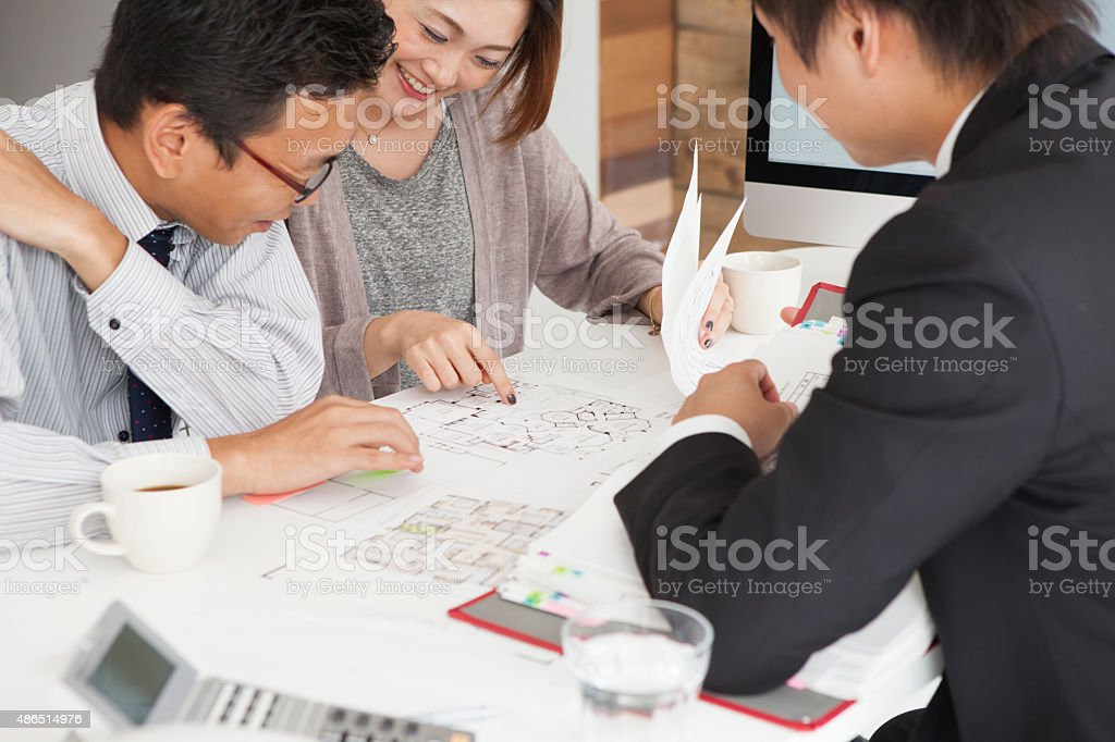 Couple meeting architect for house construction stock photo