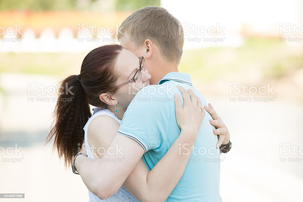Couple meeting on the street and embracing one another tightly stock photo