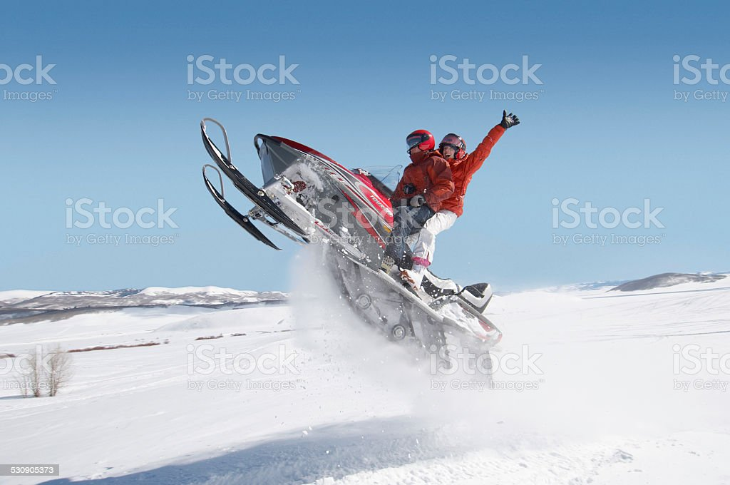 Couple Mid-air on Snowmobile stock photo