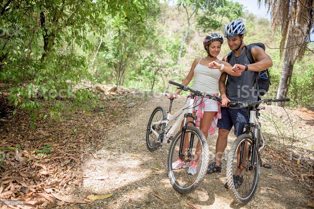 Couple mountain biking using a smart watch stock photo