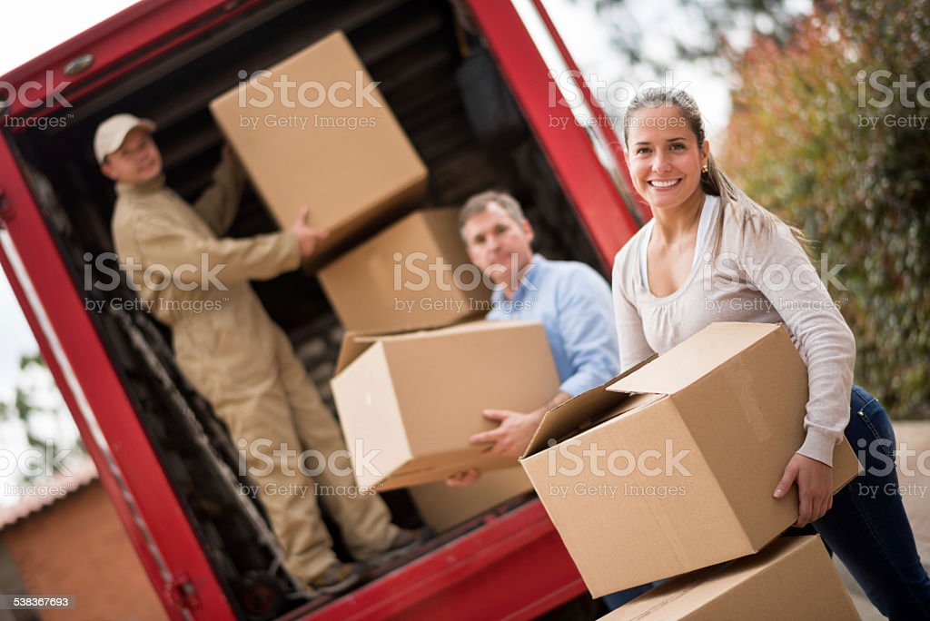 Couple moving and movers loading the van stock photo