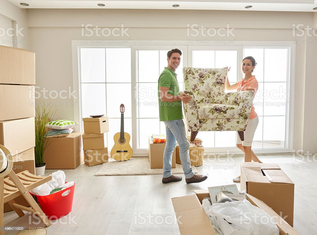 Couple moving armchair together stock photo