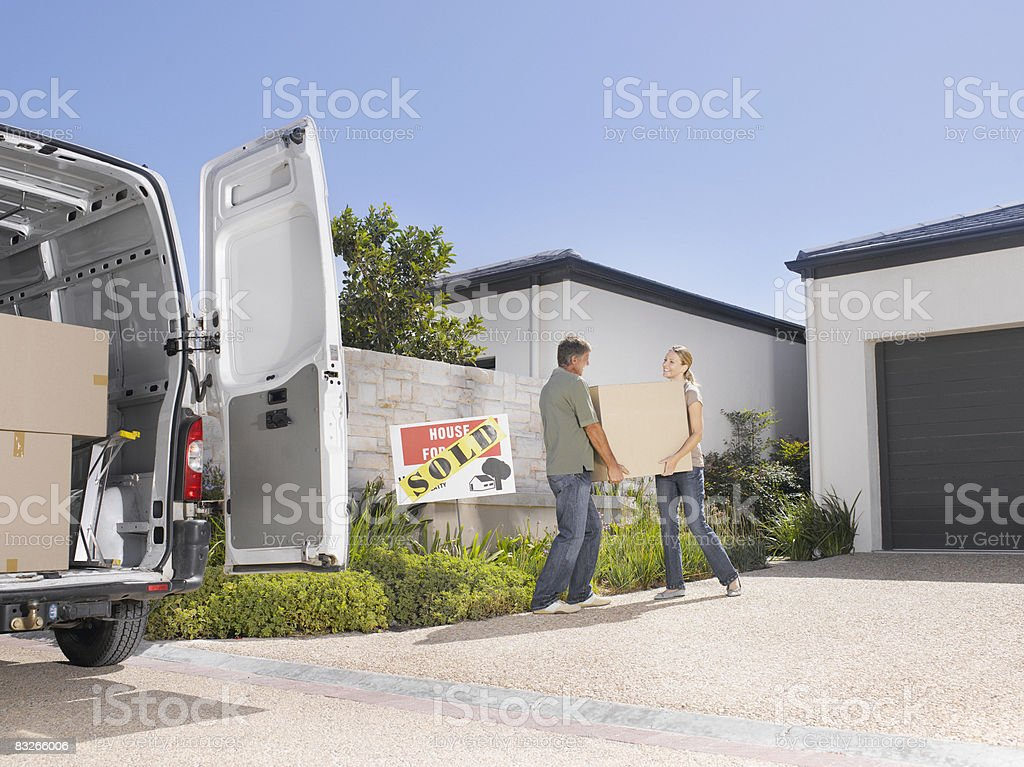 Couple moving boxes into new home royalty-free stock photo
