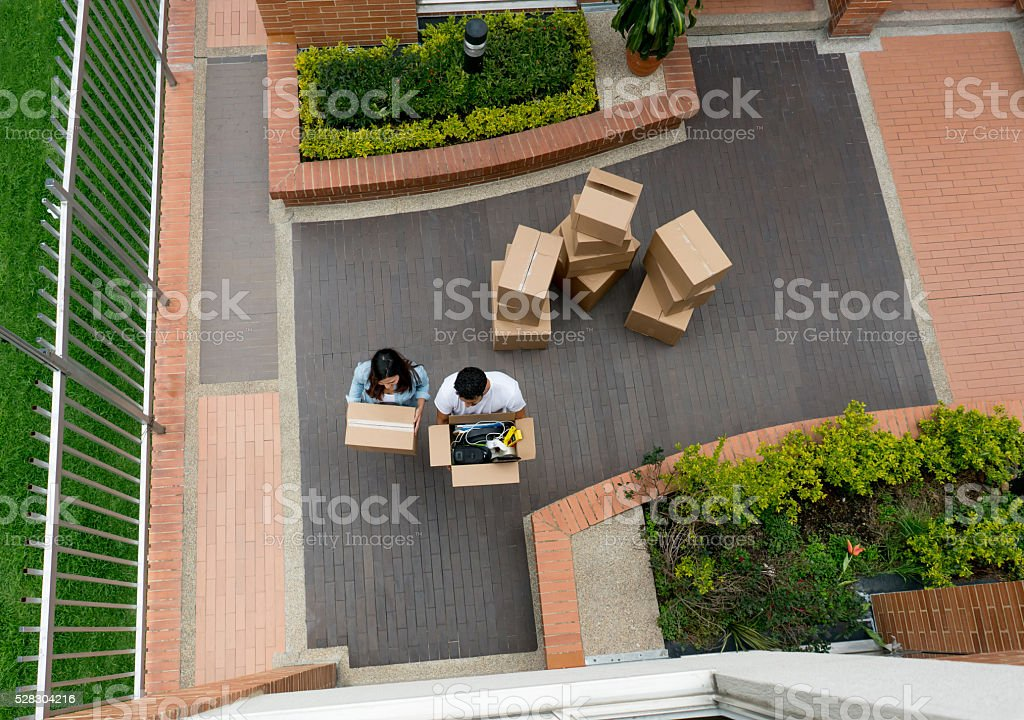 Couple moving house and carrying boxes stock photo