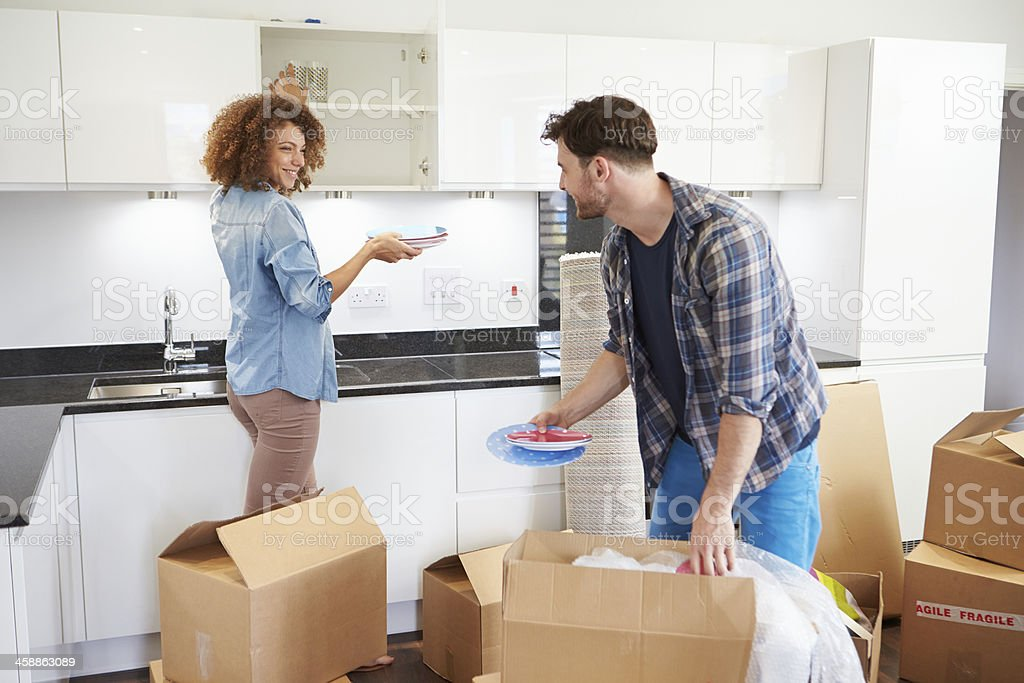 Couple Moving Into New Home And Unpacking Boxes stock photo