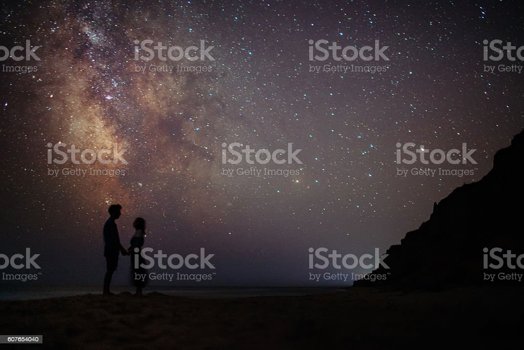 Couple near the sea under the starry sky stock photo