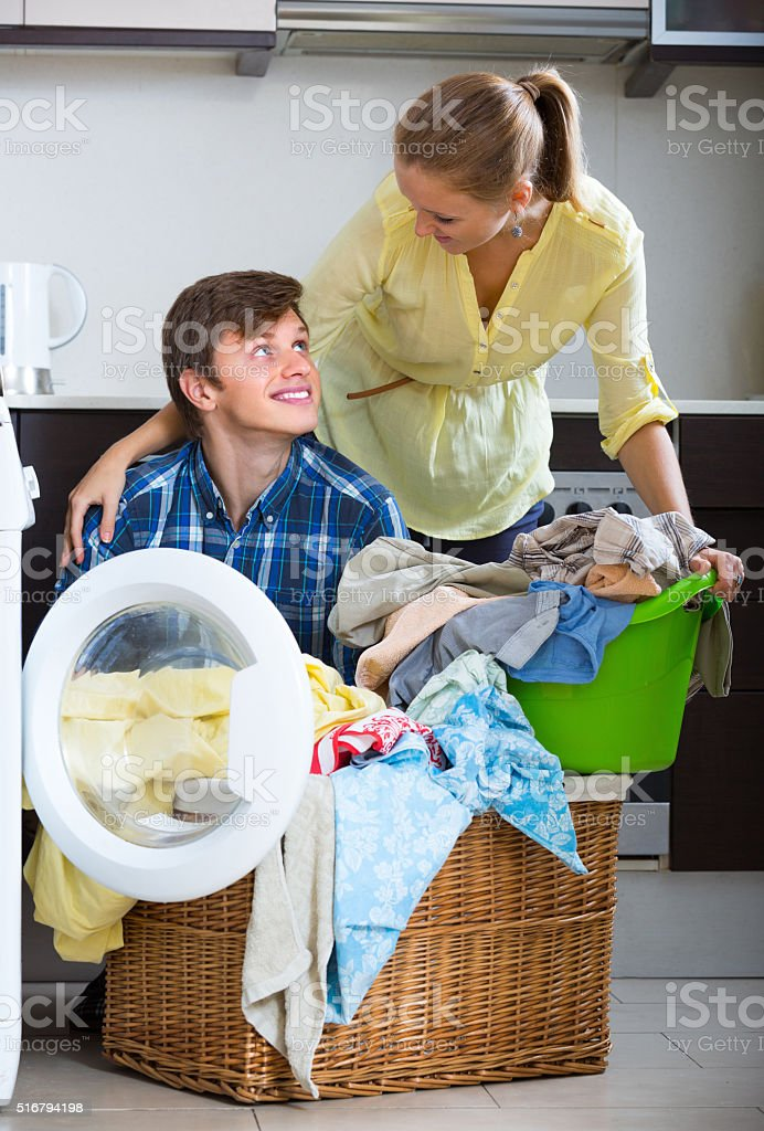 Couple near washing machine at home stock photo