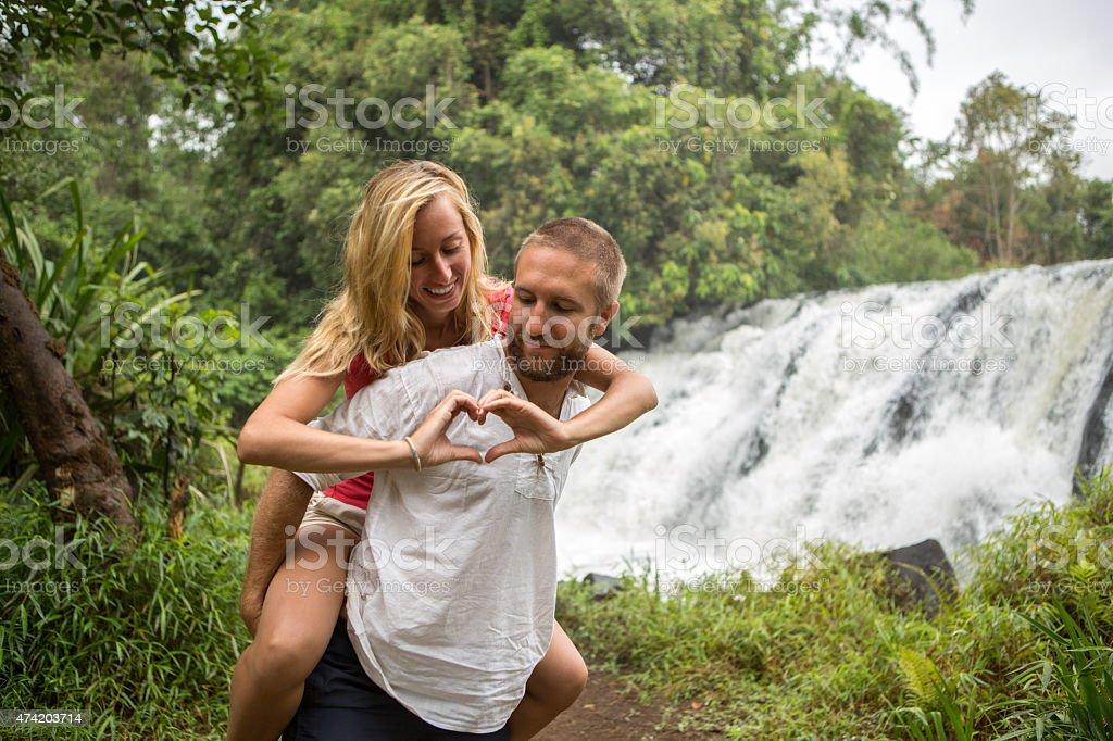 Couple near waterfalls, woman making heart shape stock photo