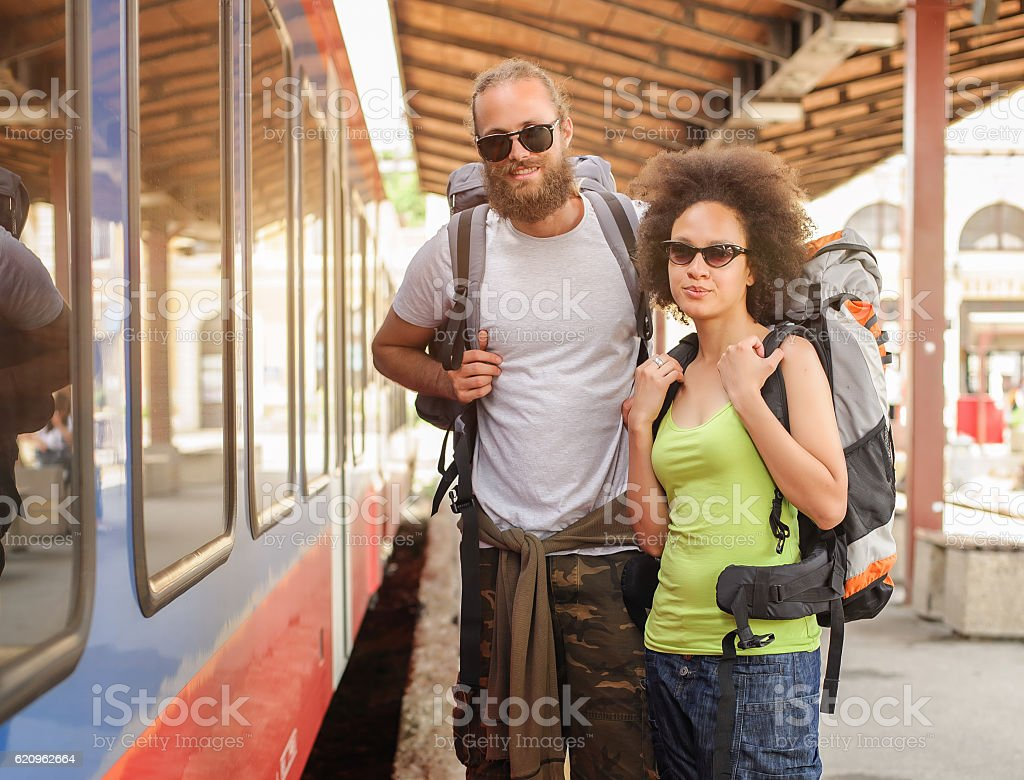 Couple of backpacker tourists waiting to board a train stock photo