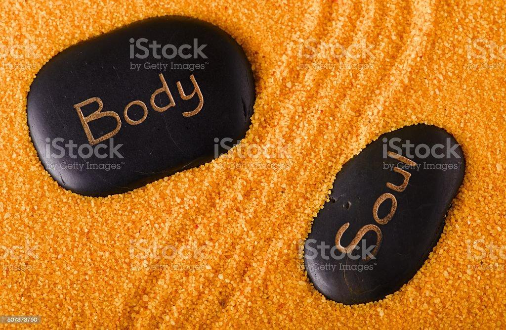 Couple of black lava stones in yellow sand stock photo