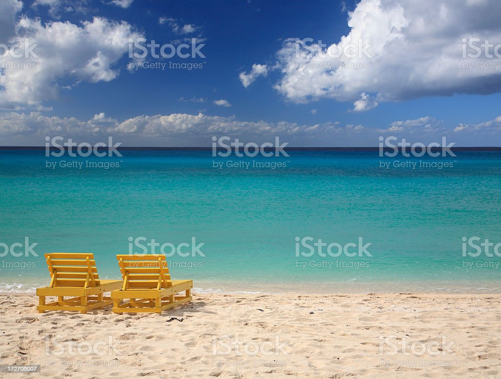 couple of chairs on the beach stock photo
