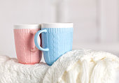 Couple of cups with knitting pattern, pink and blue color