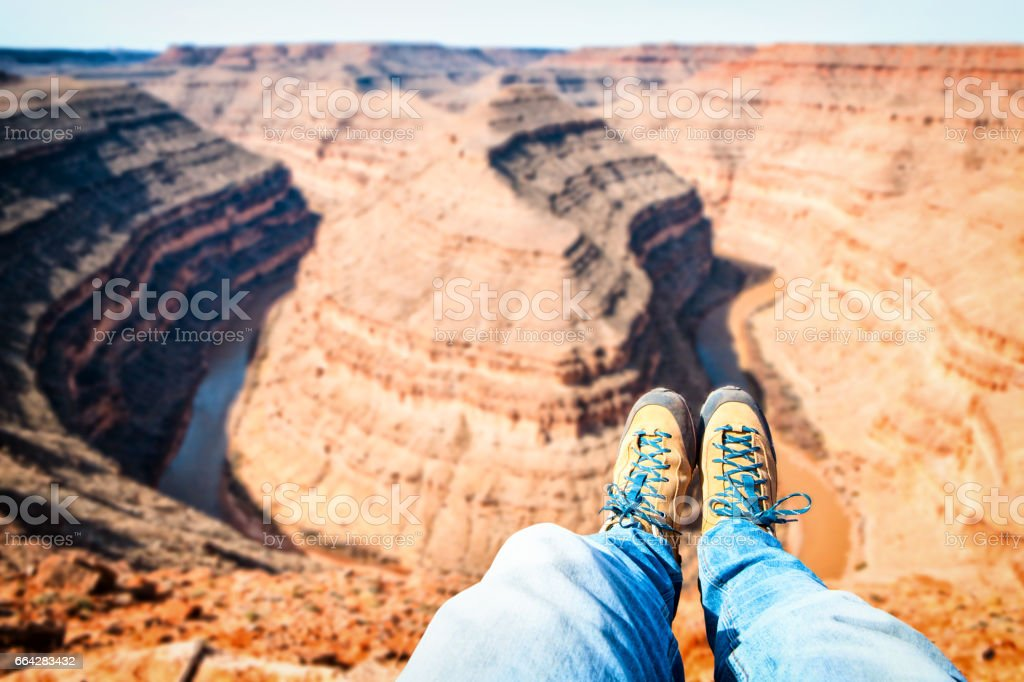 PHOTOS IN FIRST PERSON OF A couple of feet with shoes OF A BOY STANDING ON TOP OF A MOUNTAIN - GOOSENECK CANYON PARK IN UTAH USA stock photo