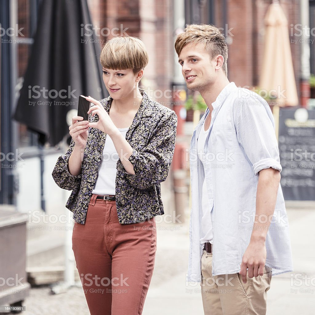 couple of friends taking a picture with smartphone royalty-free stock photo