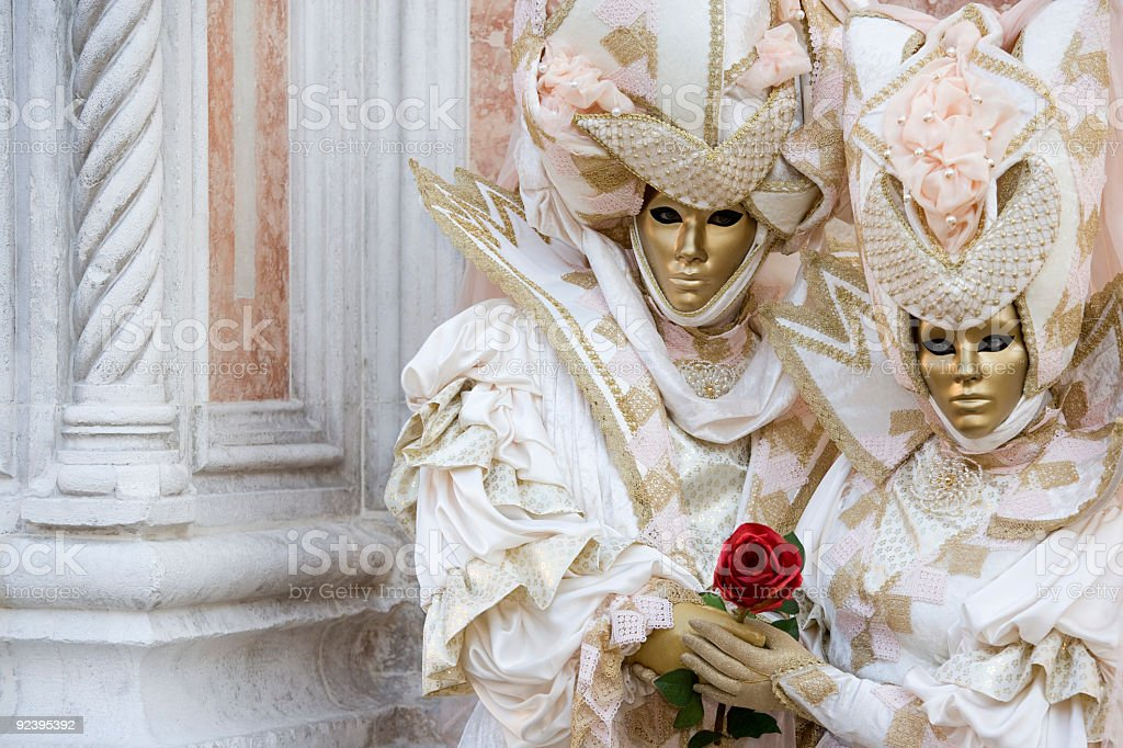 Couple of golden venetian masks in beautiful creative costumes (XXL) royalty-free stock photo