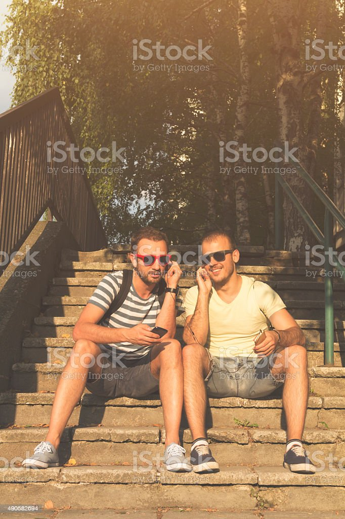Couple of guys sharing music and singing with a cellphone. stock photo