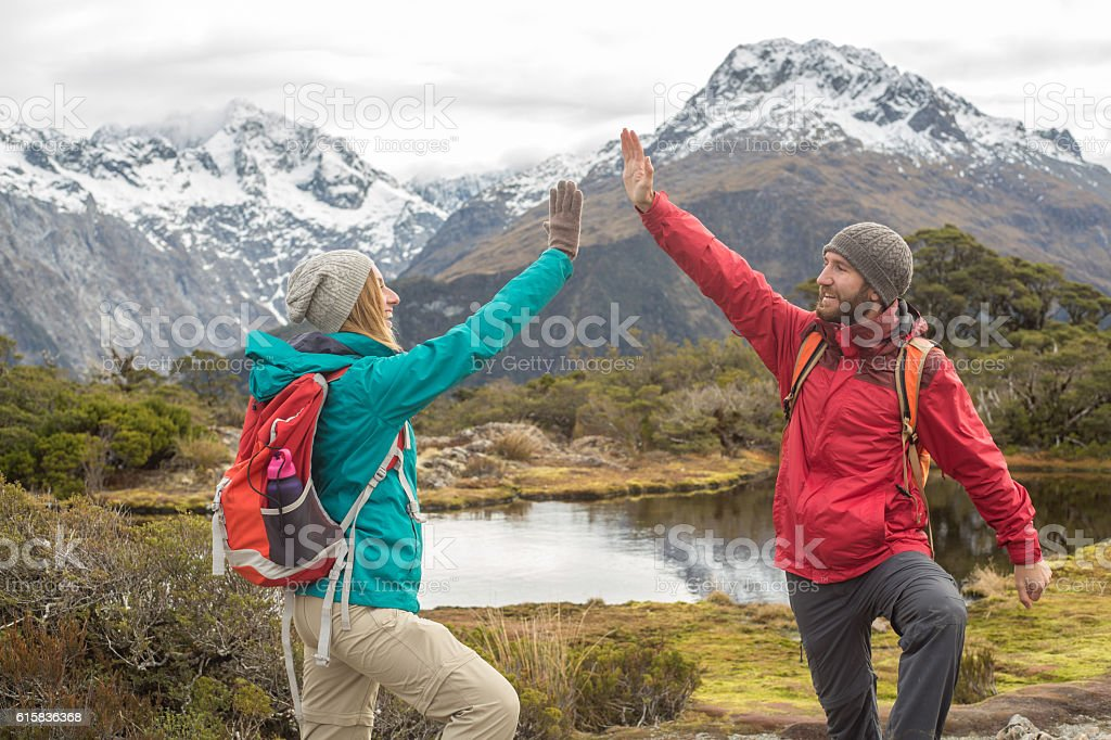 Couple of hikers celebrating on mountain top stock photo