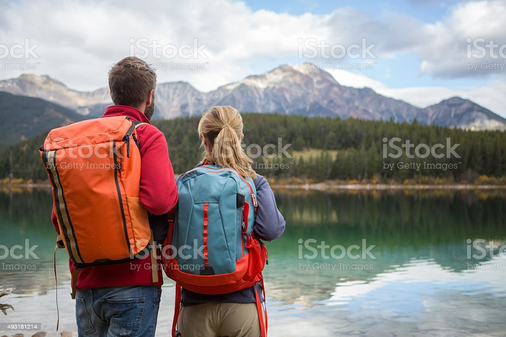 Couple of hikers contemplating the beautiful landscape stock photo