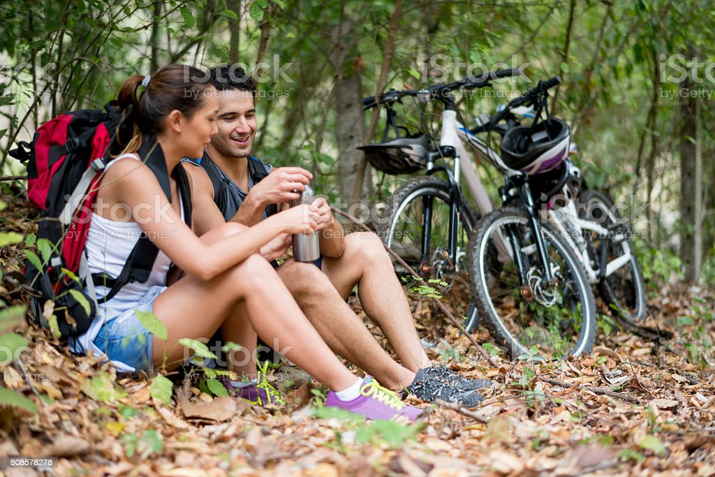 Couple of hikers drinking water stock photo