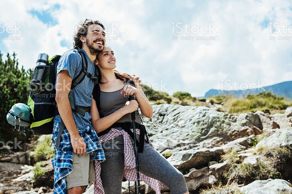 Couple of hikers enjoying the mountain view stock photo