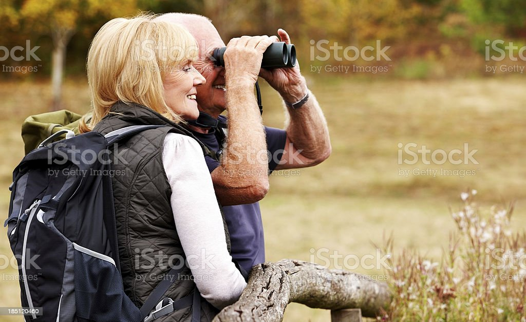 Couple of hikers looking away through binoculars royalty-free stock photo