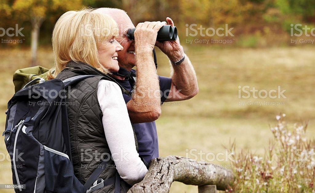 Couple of hikers looking away through binoculars stock photo