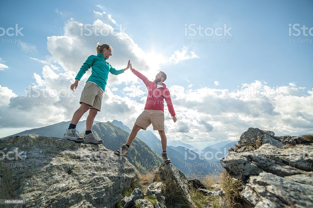 Couple of hikers reaching the mountain top celebrating stock photo