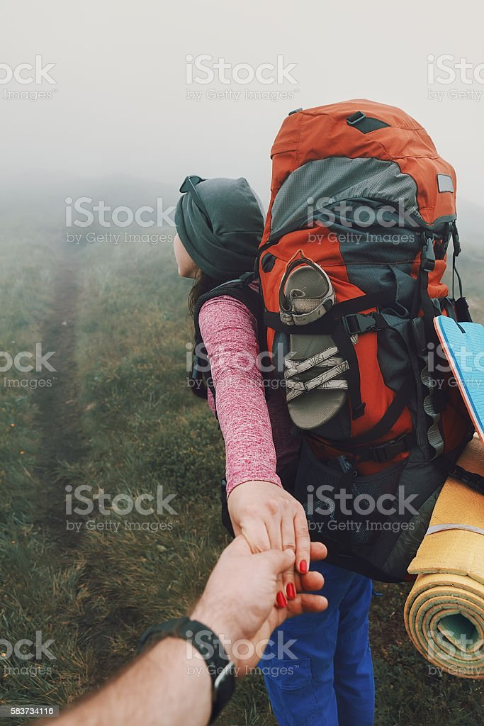 couple of hikers walking on footpath in the mountains stock photo