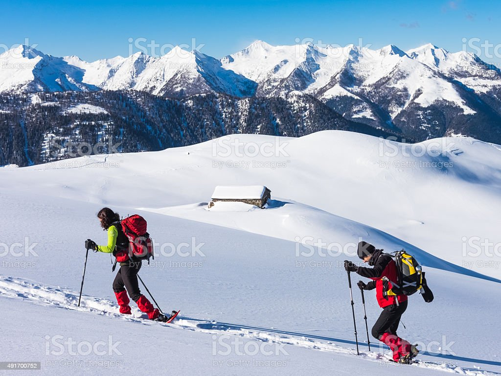 Couple of hikers with snowshoes stock photo
