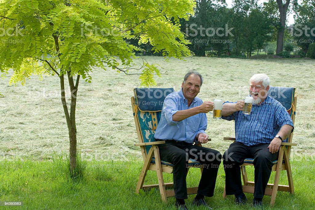 Couple of laughing seniors drinking beer in the garden royalty-free stock photo