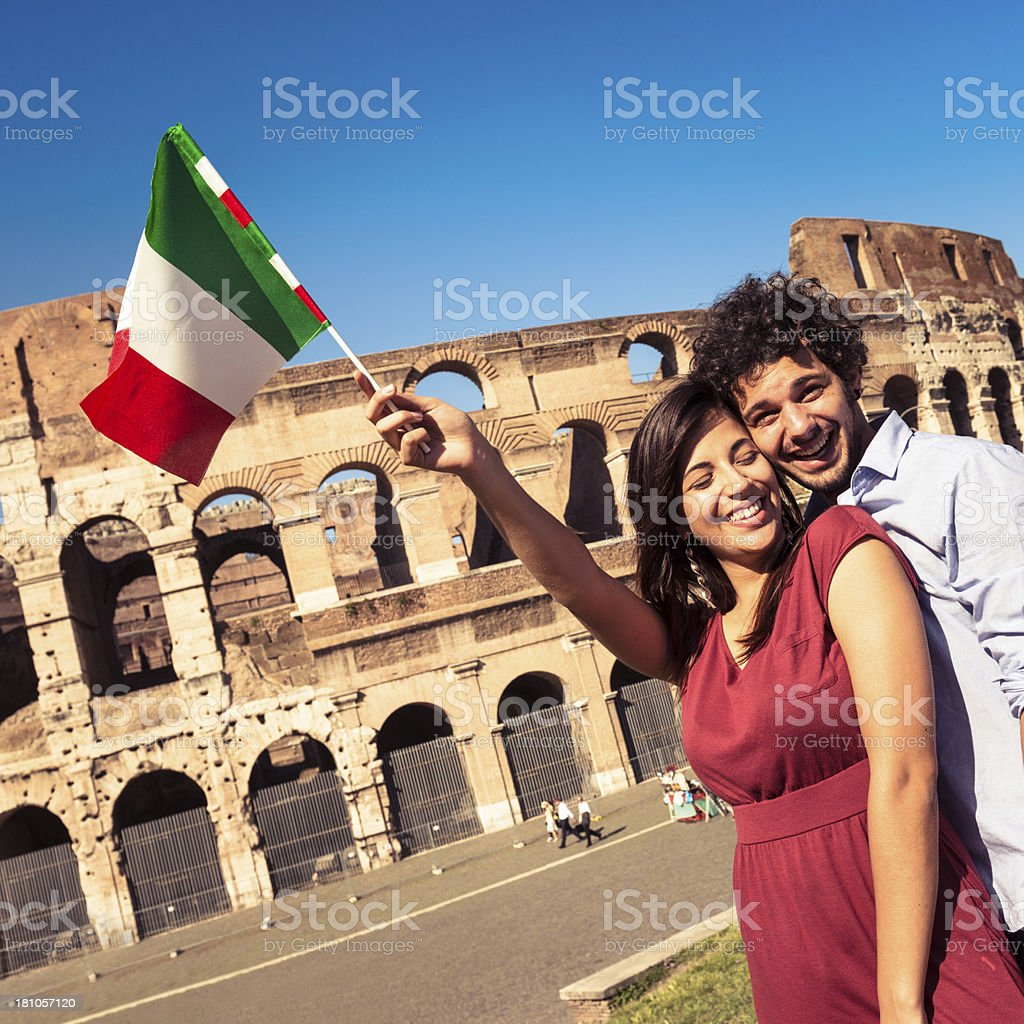 couple of lover at coliseum waving italian flag royalty-free stock photo