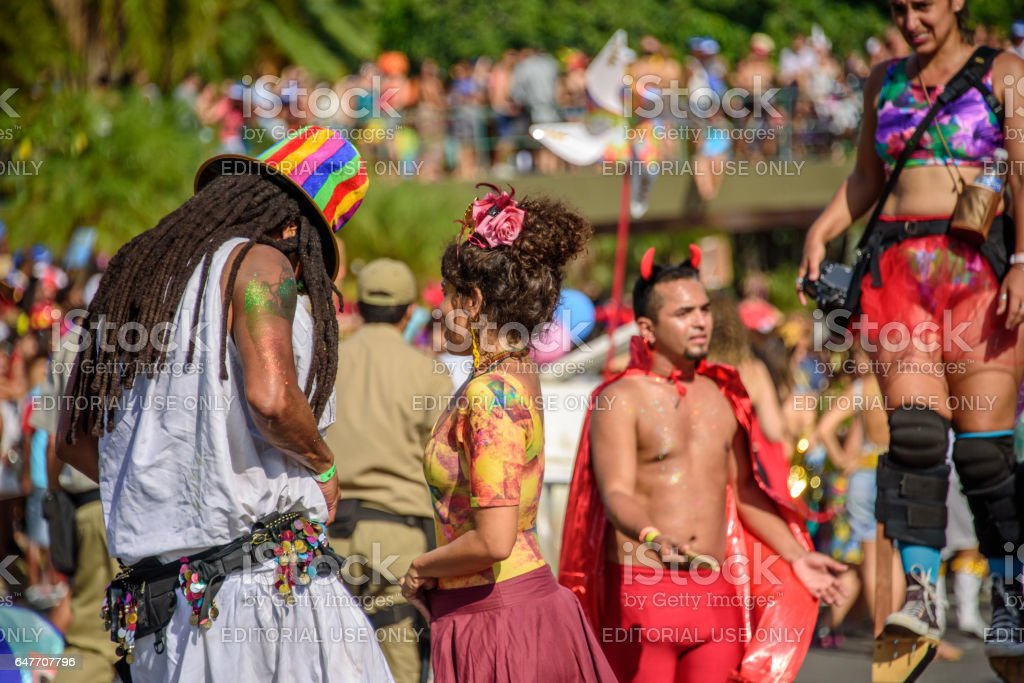 Couple of man with dreadlocks and young woman on the background of blurry man in devil costume and woman walking on stilts stock photo