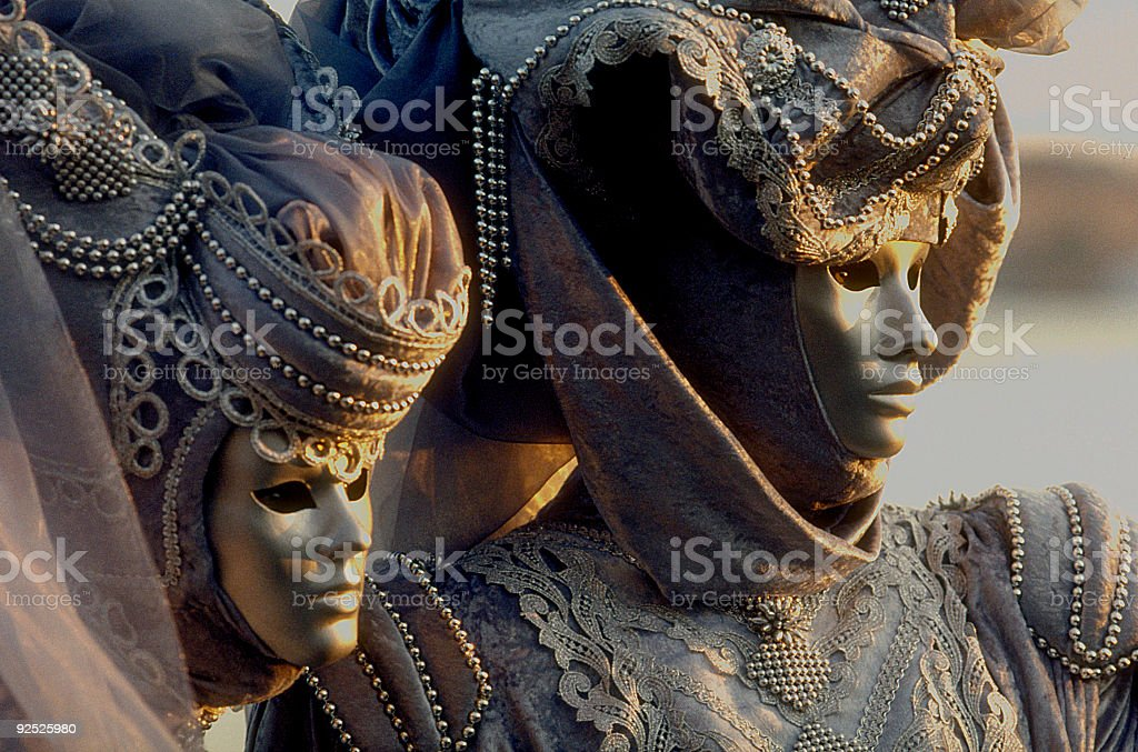 Couple of masks with beautiful costumes at carnival in Venice stock photo