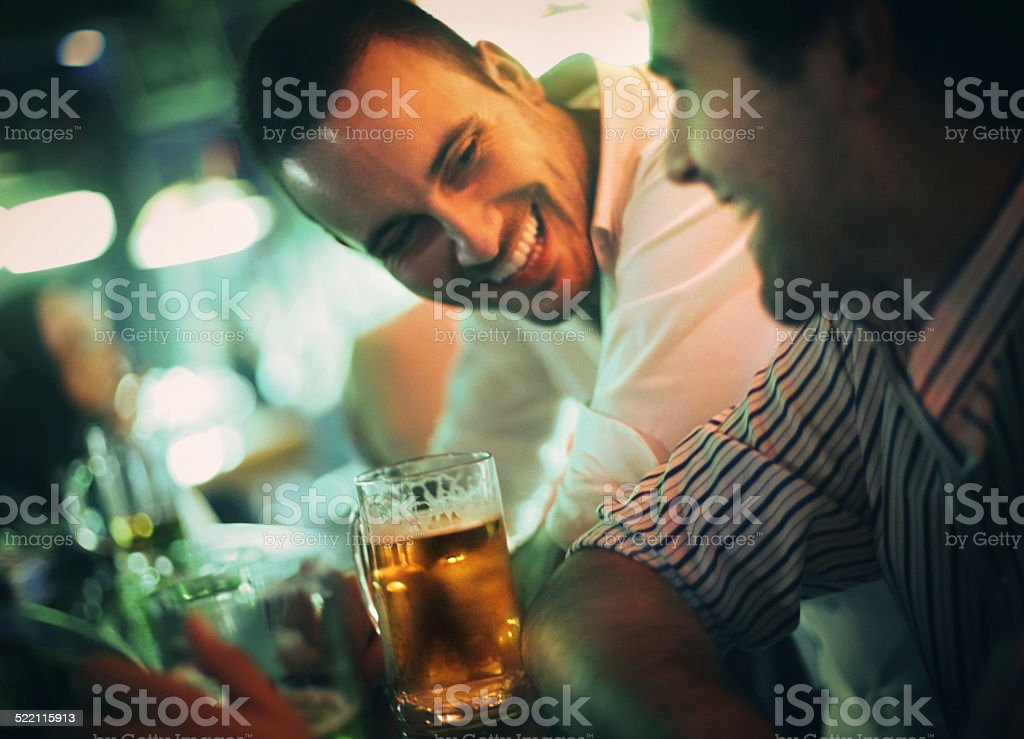 Couple of men having beer on a night out. stock photo