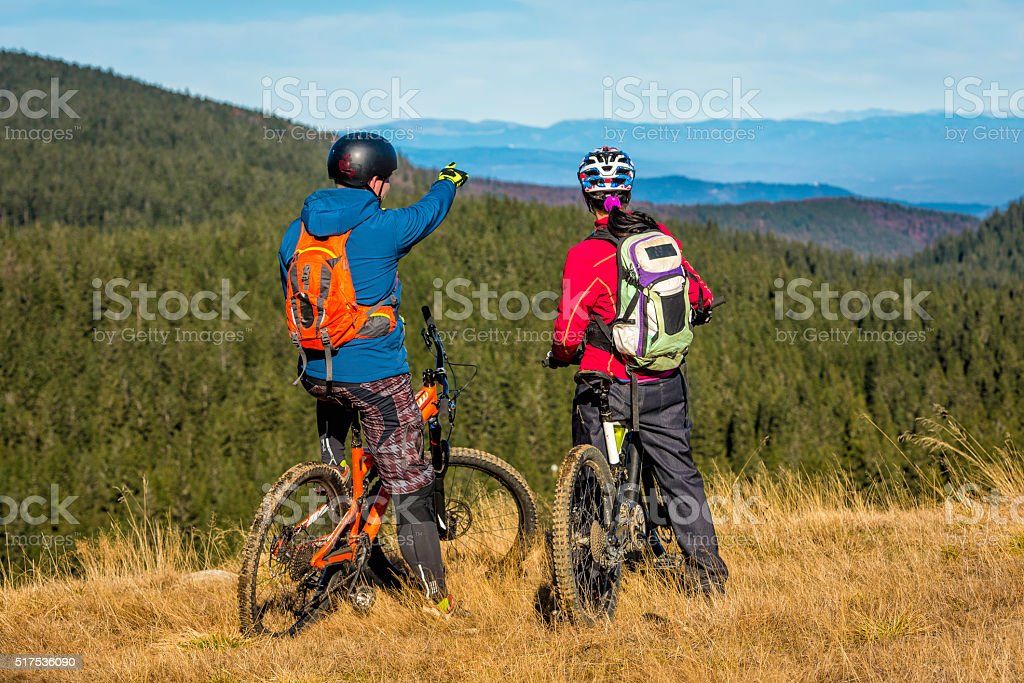 Couple of mountain bikers on top of hill observing landscape stock photo