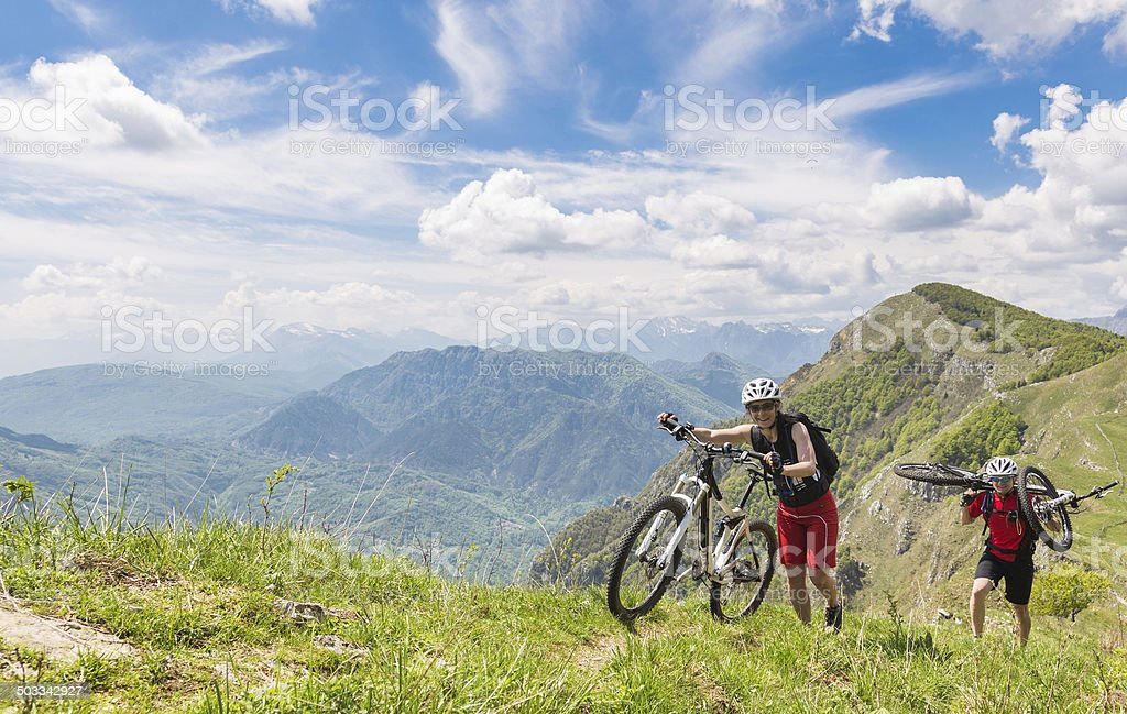 Couple of mountainbikers at the rim, Italy stock photo