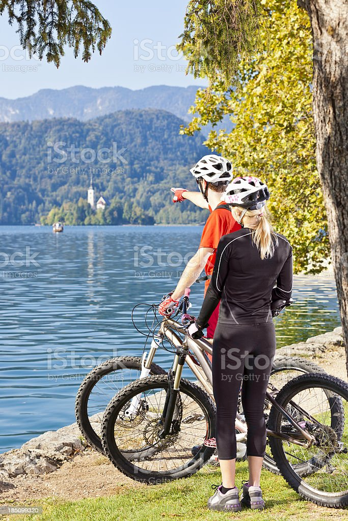 Couple of mountainbikers looking at Bled lake island royalty-free stock photo