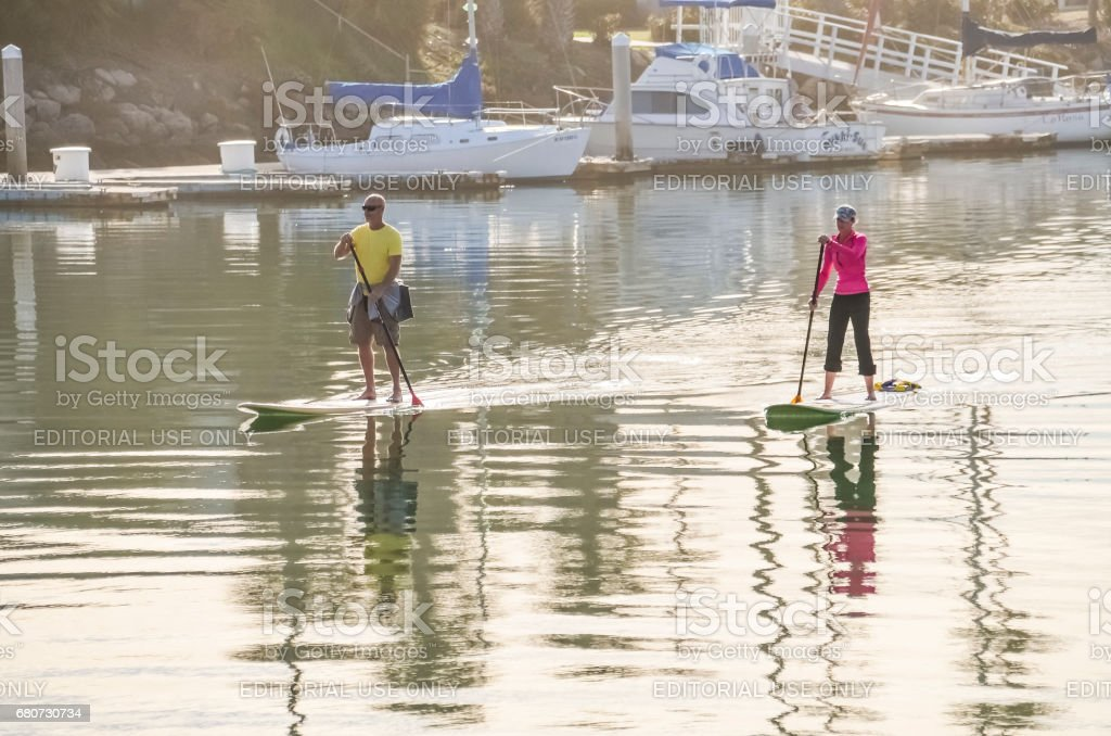 Couple of people paddleboard surfing on calm water on bay in California stock photo
