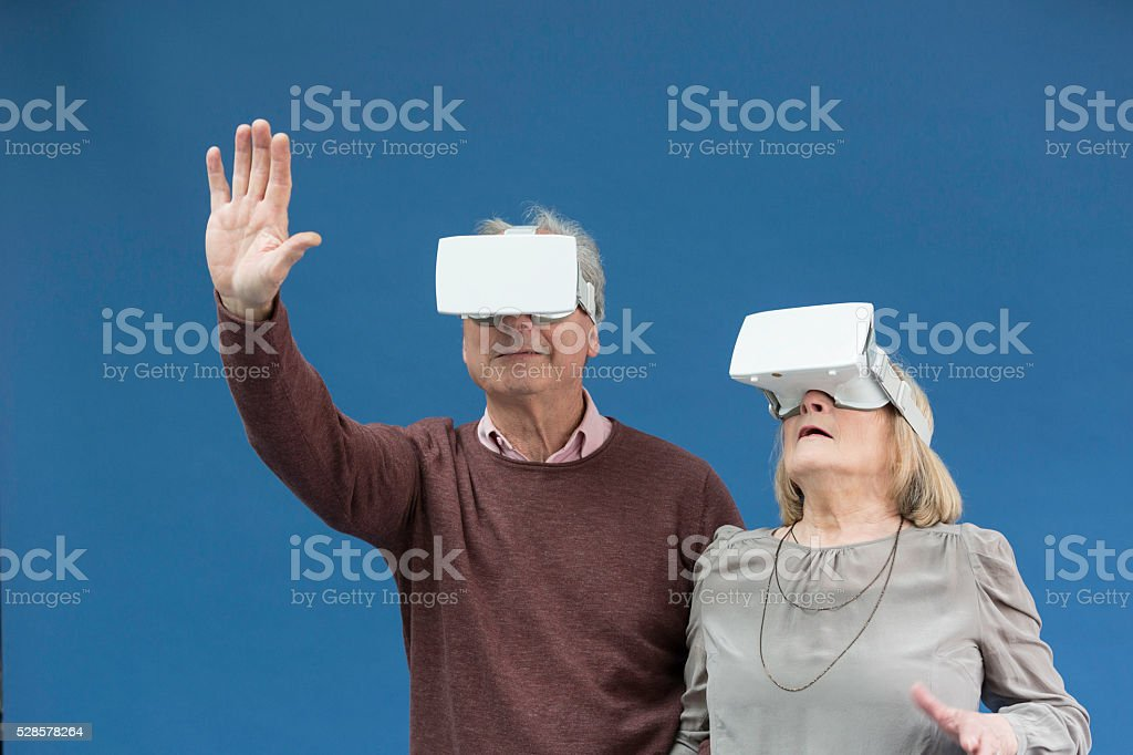 Couple of senior surprised while using virtual reality glasses stock photo