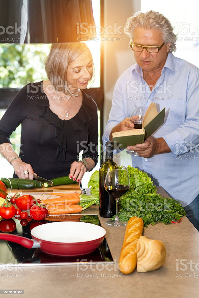 Couple of seniors cooking and reading cookbook stock photo