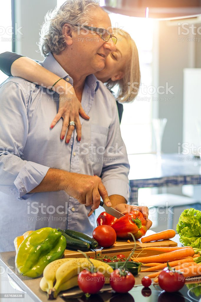 Couple of seniors in love cooking stock photo