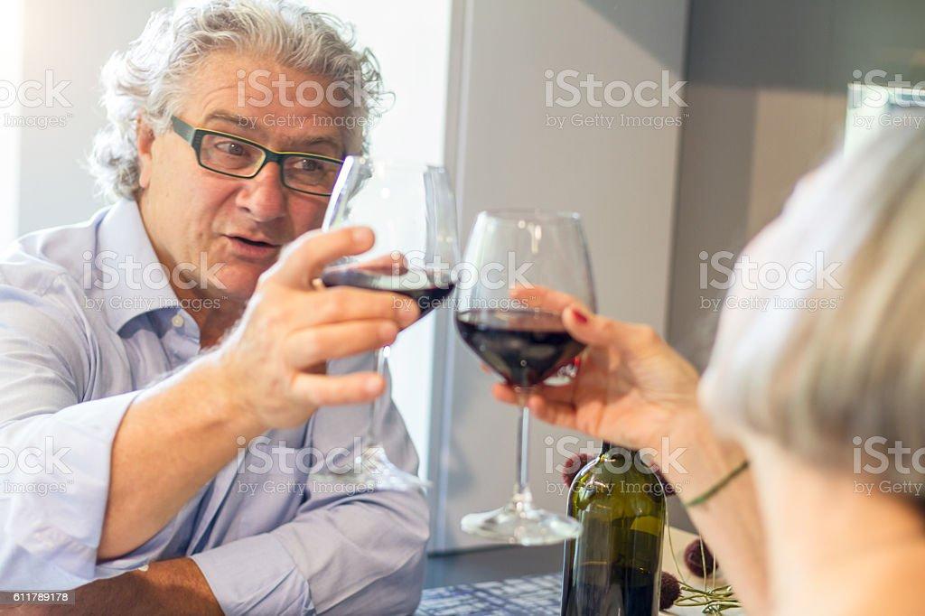 Couple of seniors tasting wine at home stock photo