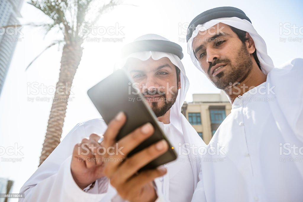 couple of sheikh friends surfing on the city stock photo